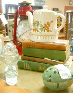 Vintage ceramic tea pot, vintage lantern, antique books. Check out our website http://www.phantasticphinds.com