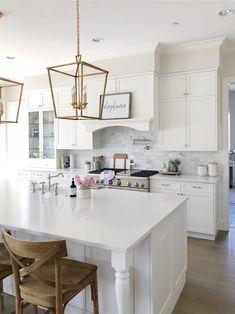 White kitchen with quartz counters, wood stools, brass lanterns, farmhouse sink and pretty spring details. #kitchendesign #homedecor #kitchenideas #springdecor
