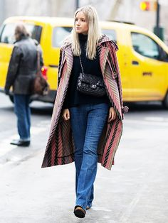 A printed trench coat is paired with a black turtleneck sweater, flared jeans, boots, and a crossbody Chanel sequin flap bag