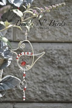 Our New Crimson Bird. This sun-catcher has red & clear glass beads with a dangling heart shaped pendant and beads. All sun-catchers come with a matching hangers. . $32.00