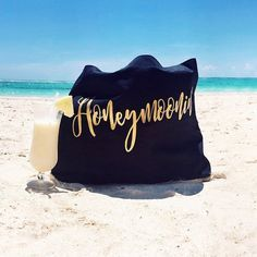 "A black jumbo tote bag with gold ""Honeymoonin'"" print and cream handles. It makes a great beach bag or carry on! Would make a perfect gift for any bride to use on her honeymoon. 100% cotton canvas, na"