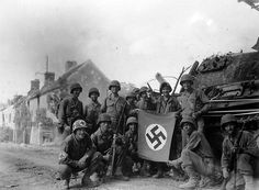American soldiers pose with a Nazi Flag next to a German Tank Destroyer in Falaise, France, 1944.
