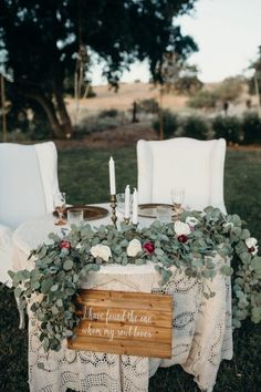 This sweetheart table channels some serious backyard romance with a lace tablecloth, gold tapered candlesticks, and gorgeous heaps of greenery.