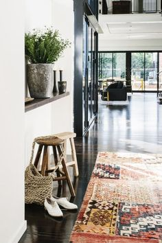 I'm going to assume this is a foyer or entryway of some sort due to the styled cues of the bag and shoes. Beautiful rug and rustic stools, planter looks metallic and weathered...Nice contrasts in this design that mixes old and new, weathered and polished (dig the floors!).