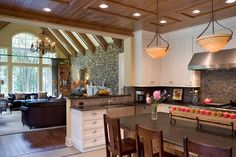 The great room and kitchen share an open living space but the ceiling differences make for a perfect transition from one space to the other
