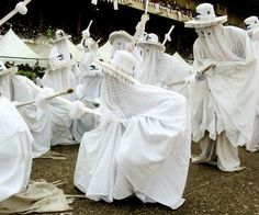 Eyo Olokun masquerades in Lagos, Yorubaland. Eyo Olokun is connected with Olokun, the Yoruba Orisha of the sea.     It works closely with Oya (Deity of the Winds) and Egungun (Collective Ancestral Spirits) to herald the way for those that pass to ancestorship, as it plays a critical role in Iku, Aye and the transition of human beings and spirits between these two existences.