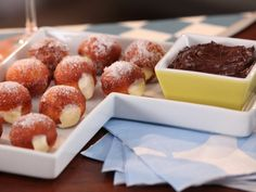 Bobby spikes these little fried balls with orange liqueur (in the pastry cream and also the dipping sauce), and rolls the warm dough in cane sugar directly out of the frying pan.