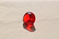 """Some synthetic gemstones are clearly labeled as such.  Dangers arise for gem buyers when gems are labeled incorrectly in the marketplace, whether in error or deliberately.  """"Ruby (Fake)"""" by maicos is licensed under CC By 2.0. [Read article at www.gemsociety.org/article/guide-to-gem-synthetics-treatments-and-imitations]"""