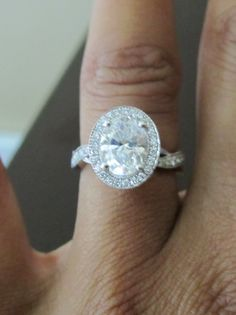 1.6 carat oval cut diamond in a platinum four prong micro pave diamond setting with infinity band.