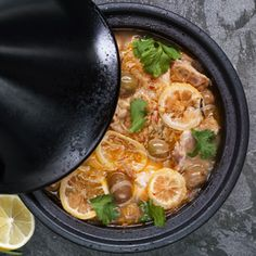 Kiptajine met olijven, citroen en koriander met bulgur - Een tajine is een van oorsprong Marokkaanse aardewerken stoofpan met een relatief hoog kegelvormig deksel. Alles wat lekker lang en rustig gaar mag stoven, is geschikt om in een tajine klaar te maken (maar een gewone braadpan gebruiken mag natuurlijk ook). Zoals kip bijvoorbeeld, met Noord-Afrikaanse smaken!