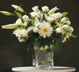 Photo about A view of a nicely arranged bouquet of white flowers and green leaves in a large vase, sitting on a white table top against a dark background. Image of bouquet, flowers, background - 2396354 Funeral Flower Messages, Funeral Flowers, Abstract Flowers, Colorful Flowers, White Roses, White Flowers, Sympathy Card Messages, Rose Arrangements, Clear Glass Vases