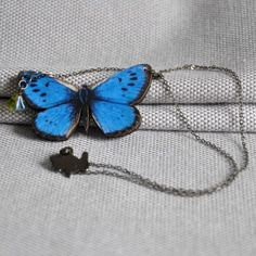 Blue Emperor Butterfly Necklace from ArtySmartyShop.com  These beautiful handmade butterfly necklaces are made from illustrated wood and hung on a gunmetal chain and clasp with a coloured Czech glass bead.  #fashion #giftideas #girlpower #nature