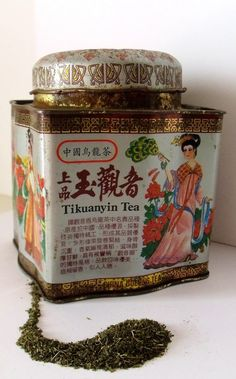 Tikuanyin Tea tea tin with Chinese lettering and Chinese scenes on the sides, square with serpentine sides and dome lid