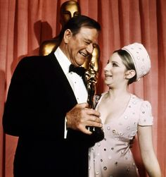 1969: John Wayne accepts his Best Actor Oscar for True Grit from Barbra Streisand