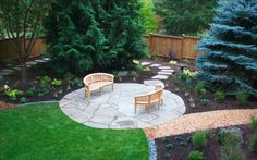 Gravel lawn border, flagstone circular patio, rounded benches.  Love this backyard, and all the separate spaces.