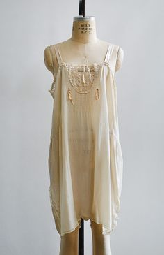 $108.00 Vintage 1920s pale cream silk chemise step in. Vintage early 1920s step-in has horse shoe shaped lace insert at bodice, pin tucks along center, pastel silk ribbon accents, and curved stitch detail on side of hips.