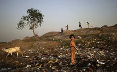 An Afghan refugee girl takes a break from searching for useful items in a pile of garbage next to a slum area on the outskirts of Islamabad, Pakistan.