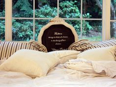 A headboard doesn't have to span the entire width of the bed. Designer Melaine Thompson painted an old round frame to match the four-poster bed then painted a piece of wood with chalkboard paint. This budget-friendly headboard allows the mind to be creative by being able to write different messages.