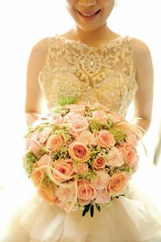 The bridal bouquet was made of pink and peach roses and ostrich feathers.   Flowers by Vatel Manila   www.BridalBook.ph