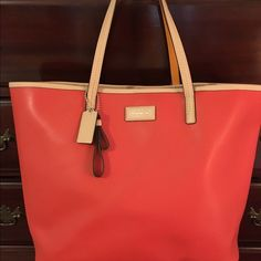 """NWT Coach tote Beautiful orange leather bag with tan leather trim. This bag is large in fact in would make a great beach bag. Bought but never used.  Color is called vermillion. This bag retails for 328.00 so this is a great steal. It measures 17""""x 12.5""""... Coach Bags Totes"""