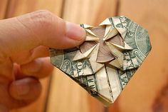 How to Fold a Dollar Into a Heart. Make money a little more fun by folding a dollar bill into a basic heart shape. You can also take it a step further if you're more advanced at origami by adding a pocket that holds a quarter, too. Paper Hearts Origami, Origami Stars, Origami Paper, Diy Paper, Paper Crafts, Origami Boxes, Origami Ball, Diy Origami, Origami Flowers