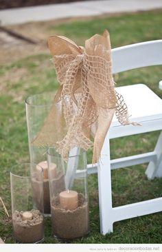 Decoración de boda en jardín con sillas, velas con arena y lazo de yute
