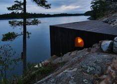 Lakeside sauna by Partisans designed as a cavernous wooden grotto