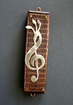 """Perfect mezuzah to give your cantor! Made of etched copper and sterling silver. This features a treble clef combined with the Hebrew letter """"shin"""", standing for peace, God, and the first word of the most holy prayer, the """"Shema."""" Beautiful way to incorporate Judaism and music for your home or office! Handmade by Ruth Shapiro."""