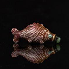 CHINE - XVIIIe/XIXe siècle  Flacon tabatière en forme de poisson émaillé en rouge de fer. Bouchon en jadéite.  H.4,1 cm