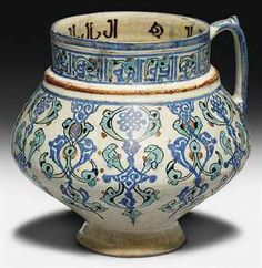 A MINA'I POTTERY JUG IRAN, CIRCA 1200 Rising from slightly spreading conical foot through rounded bulbous body to pronounced collar, the vertical mouth with slightly flaring rim and simple loop handle with knop, with white ground painted in a variety of overglaze enamel colours, the body with hanging lattice medallions surrounded alternately by scrolling vegetation and stylised birds, the shoulder with a red band, the mouth with psuedo-calligraphic decoration.