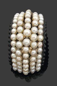 ~Suzanne Belperron (Attribué à). Années 1935~   Rare clip de revers de forme bombée composé de rangs de perles de culture (quelques perles fines) disposées en chute et bordées de boules laquées noir. Monture en argent. (infimes rayures à la laque). Dimensions: 4,3 x 2,2 cm