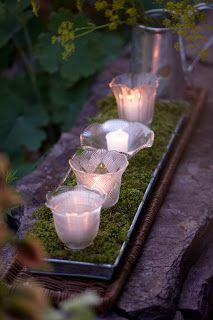 Chandelier globes from the flea market make great votives for candles in metal plant tray lined with moss...