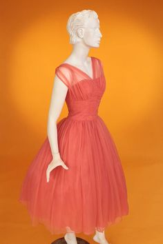 A fabulous original vintage 1950s floaty, gathered chiffon and net prom dress! The main dress is strapless with a structured bodice with boning. The main dress is overlaid with net and a synthetic chiffon. The chiffon has been gathered around the bust line and creates the gathered