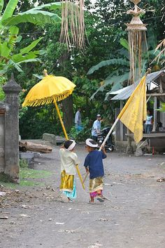 Kids with an umbrella and flag, Bali, Indonesia