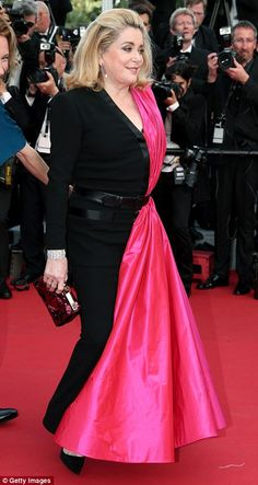 Leading star: Catherine Deneuve stole the show in a black and vibrant pink gown as she mad...