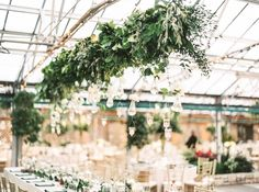 Again, hanging tea lights are mixed with a greenery installation. Here, the greenhouse venue really lets the hanging greens stand out, don't ya think?!