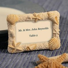 Beach Design Wedding Place Card Holder made of poly resin made to resemble sand. It is decorated with poly resin seashells and starfish. Each one includes a place card. They come packaged in a white gift box.