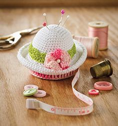 A diminutive Summer hat which is really a Pin cushion and place to keep your measuring tape ~ free pattern; also included is an excellent crochet pattern symbols / abbreviations chart, and easy instructions for making all the necessary basic stitches
