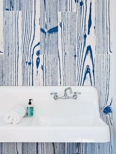 An Idyllic Rhode Island Summer Cottage Is the Perfect Escape for a New York Family - Photo 7 of 16 - White-and-blue, wood-grain–patterned UonUon tiles by 14oraitaliana line the bathroom walls in a loft above the garage.