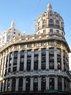 """Edificio """"""""Bencich"""""""" Data del 1927, esta en Avenida Roque Saenz Peña y Florida. Son dos edificios enfrentados, con dos grandes cupulas, de cinco pisos c/ una. Hoy es el 1° edificio de bien de Patrimonio Historico"""