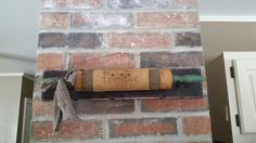Old rolling pin wrapped with homespun, set on old straight nails on primitive painted wood board , wire to hang .