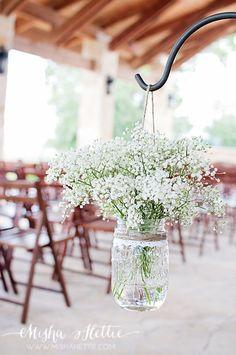 Baby's Breath in mason jars along aisle at wedding.