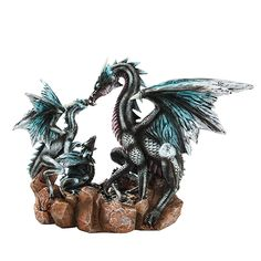 This fabulous figurine features a trio of dragons. The family includes a mother dragon and two young fledgelings, each with black, white and blue coloration. They perch in their nest, sharing a tender moment.