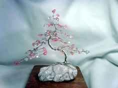 $35.00 Cherry Blossom Glass Beaded Bonsai. This beautiful cherry blossom bonsai is made with 94 Glass Simulated Cherry Quartz chips. It is hand twisted with 24 gauge silver craft wire. The base is white quartz.    Approximate Dimensions: Length 6 in (canopy length not base length), Width 3 in, Height 5.5 in. This is a one-of-a-kind piece.