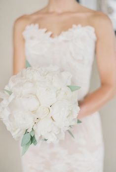 Brides.com: . For April's romantic Denver, Colorado wedding, she carried a classic bridal bouquet of white peonies with greenery accents, created by Design Works.