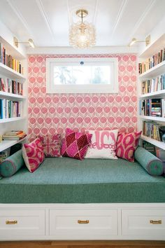Fun kid's reading nook is filled with a built-in bench with storage drawers adorned with gold pulls topped with a green bench cushion, green bolster pillows and a collection of pink pillows against a backdrop of a pink wallpapered wall flanked by built-in bookcases.