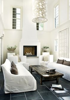 - Sunny white modern living room design with 2 story ceiling, fireplace, and all white couches, and a nice classic coffee table.