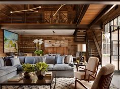 In the main living room of a Connecticut barn renovated into an inviting retreat for entertaining, a pair of chairs by Gio Ponti were reupholstered with shearling and a subtly patterned sofa adds contrast in the wood-clad space. | archdigest.com
