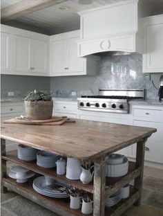 fabulous old work table used as kitchen island, white stoneware, white kitchen , tile floor