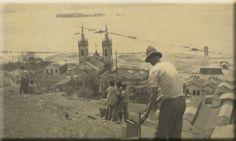 Trabalhadores no alto do morro do Castelo Vê-se adiante a praia de Santa Luzia começando a ser aterrada e o casario que havia nas franjas do morro, que foi demolido posteriormente para a abertura de ruas. Na baía da Guanabara, a ilha de Villegagnon ainda bastante afastada da costa. Hoje é ligada ao continente por uma ponte, graças aos aterros. Rio de Janeiro, [1920-1922]. Foto Júlio Ferrez. Arquivo Família Ferrez